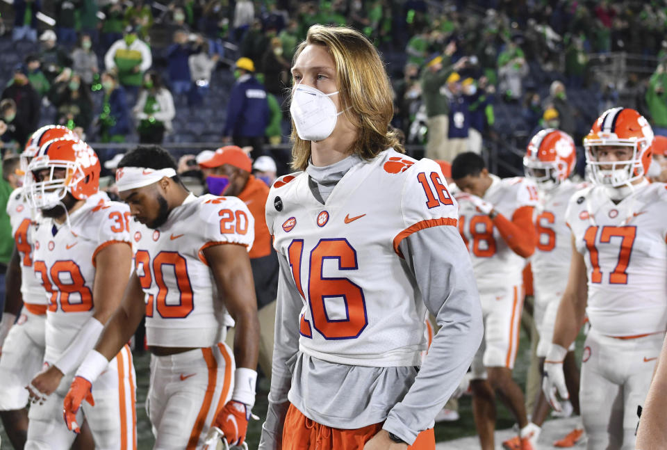 FILE - In this Saturday, Nov. 7, 2020 file photo, Clemson quarterback Trevor Lawrence (16) leaves the field with his teammates after Clemson lost to Notre Dame 47-40 in two overtimes during an NCAA college football game in South Bend, Ind. As virus disruptions mount and the Dec. 19 end of college football's regular season draws closer, the possibility grows that conference championships, major awards and even College Football Playoff participants will be determined by COVID-19. (Matt Cashore/Pool Photo via AP, File)