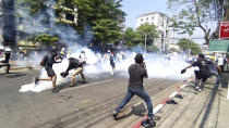 In this image from a video, anti-coup protesters run away from tear gas launched by security forces in Yangon, Myanmar Monday, March 1, 2021. Defiant crowds returned to the streets of Myanmar's biggest city on Monday, determined to continue their protests against the military's seizure of power a month ago, despite security forces having killed at least 18 people around the country just a day earlier. (AP Photo)