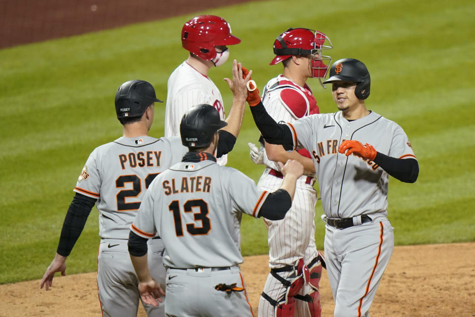 San Francisco Giants' Wilmer Flores, right, celebrates with Austin Slater, center, and Buster Posey, left, after hitting a three-run home run off Philadelphia Phillies pitcher Connor Brogdon during the eighth inning of a baseball game, Tuesday, April 20, 2021, in Philadelphia. (AP Photo/Matt Slocum)