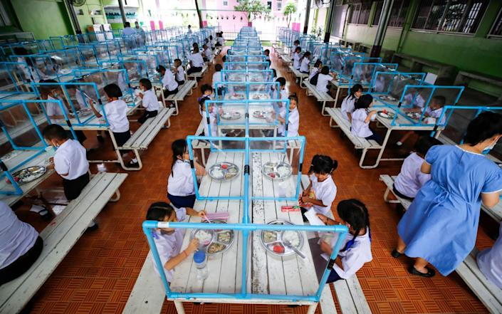 Students eat their lunch, separated from each other by plastic sheets, during the first day of school, at a school in Bangkok earlier this month - DIEGO AZUBEL/EPA-EFE/Shutterstock