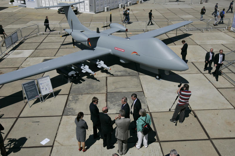 FILE In this file photo dated Monday July 14, 2008 visitors talk and wander around a Mantis unmanned aircraft  by BAE Systems PLC during a presentation at the opening day of the Farnborough aerospace show, in Farnborough, England.  Defense and aerospace companies BAE Systems PLC and EADS have hours to agree on whether to go ahead with a proposed merger that has faced opposition from Britain, France and Germany. British-based defence contractor BAE Systems and Franco-German EADS, the parent of Airbus, must reach an agreement before 1600 GMT Wednesday Oct. 10, 2012 on whether they would ask regulators for more time to finalize their plans, or abandon the deal. The proposed mega-merger, which would create a global aerospace and defense company, has been fraught with difficulties because of political objections from governments in the U.K., France and Germany. The governments, which have stakes in the companies, have fought over control of the proposed merger. All three countries must approve the deal for it to go ahead. (AP Photo/Lefteris Pitarakis)