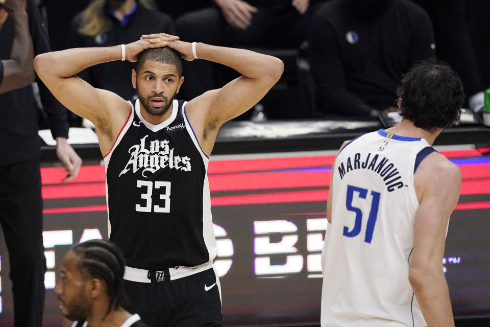 Los Angeles Clippers forward Nicolas Batum, left, reacts after the Clippers were charged with a foul as Dallas Mavericks center Boban Marjanovic walks by during the second half in Game 5 of an NBA basketball first-round playoff series Wednesday, June 2, 2021, in Los Angeles. (AP Photo/Mark J. Terrill)