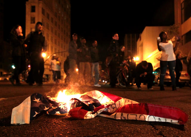 A flag burns during a protest after George Zimmerman was found not guilty in the 2012 shooting death of teenager Trayvon Martin, early Sunday, July 14, 2013, in Oakland, Calif. Protesters angered by the acquittal Zimmerman held largely peaceful demonstrations in three California cities, but broke windows and started small street fires Oakland, police said. (AP Photo/Bay Area News Group, Anda Chu)