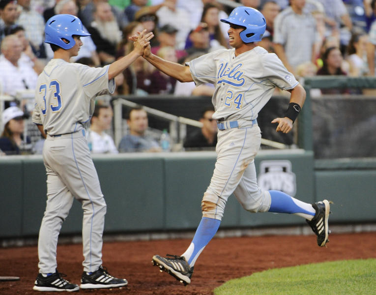 UCLA's Brian Carroll (24) celebrates with teammate Hunter Virant after he scored against Mississippi State on a two-RBI single by Eric Filia in the fourth inning of Game 1 in their NCAA College World Series baseball finals, Monday, June 24, 2013, in Omaha, Neb. Brenton Allen also scored on the play. (AP Photo/Francis Gardler)