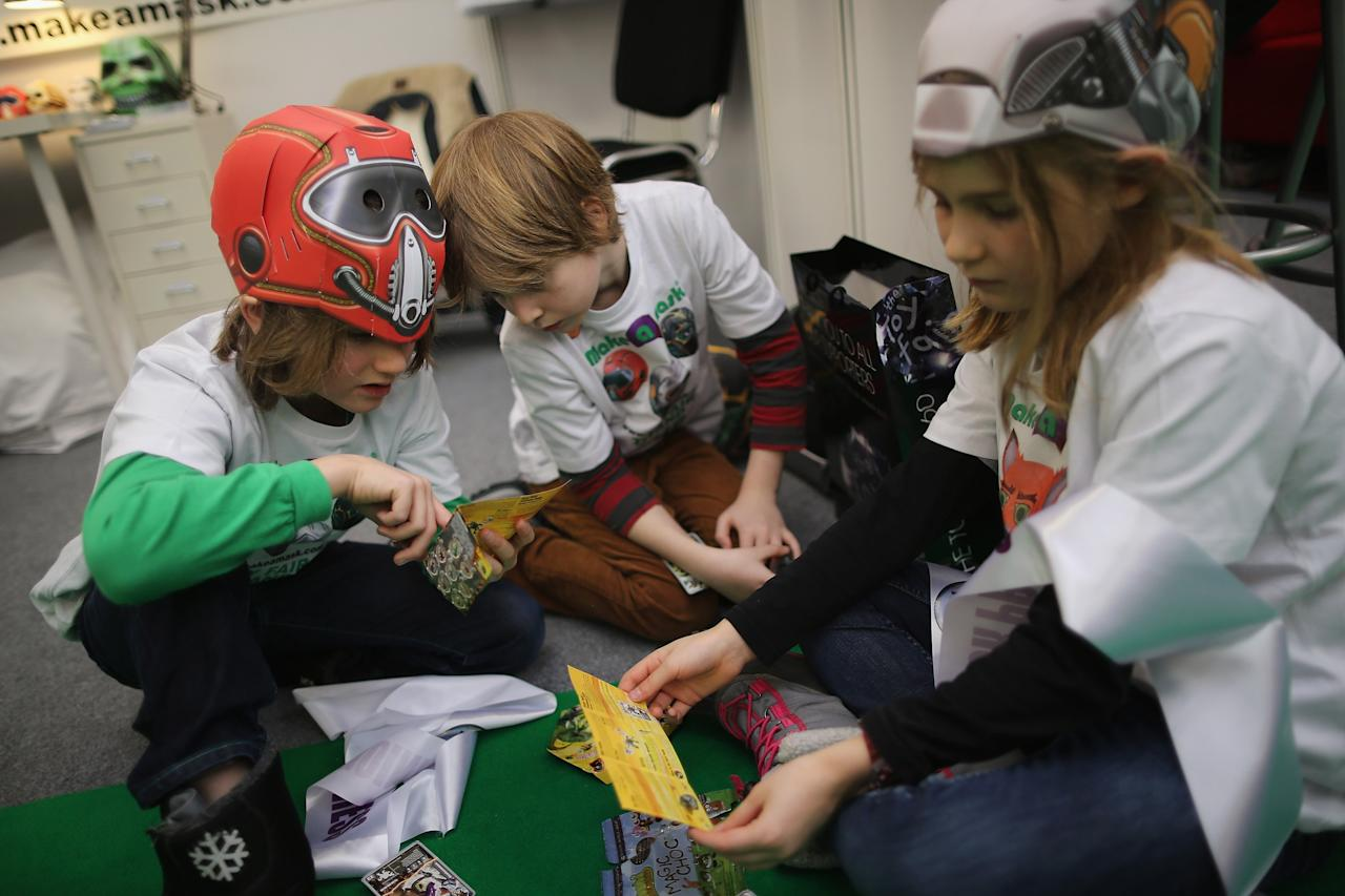 LONDON, ENGLAND - JANUARY 22:  Children make masks on a trade stand during the 2013 London Toy Fair at Olympia Exhibition Centre on January 22, 2013 in London, England. The annual fair which is organised by the British Toy and Hobby Association, brings together toy manufacturers and retailers from around the world.  (Photo by Dan Kitwood/Getty Images)
