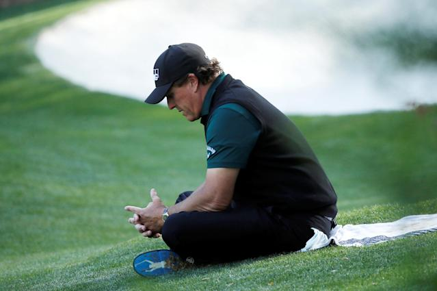 Phil Mickelson of the U.S. sits in the grass on the 13th as he waits on players in his group to finish the hole during first round play of the 2018 Masters golf tournament at the Augusta National Golf Club in Augusta, Georgia, U.S., April 5, 2018. REUTERS/Mike Segar TPX IMAGES OF THE DAY