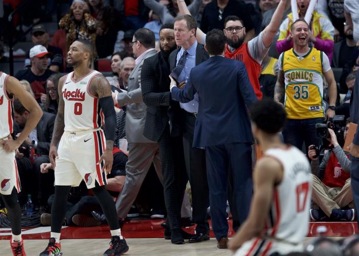 Portland Trail Blazers coach Terry Stotts, center, is held back after being ejected during the second half of the team's NBA basketball game against the Los Angeles Lakers in Portland, Ore., Friday, Dec. 6, 2019. (AP Photo/Craig Mitchelldyer)