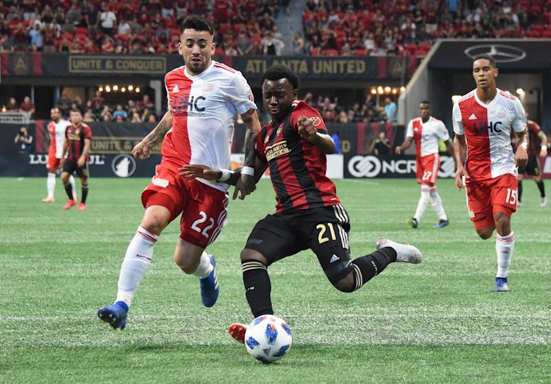 Oct 6, 2018; Atlanta, GA, USA; Atlanta United defender George Bello (21) in action against New England Revolution forward Guillermo Hauche (22) during the first half at Mercedes-Benz Stadium. Mandatory Credit: Adam Hagy-USA TODAY Sports