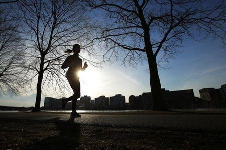 A woman jogs along the Charles River on an early spring evening in Boston