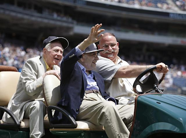Hall of Fame pitcher Whitey Ford, left, laughs as former teammate and Hall of Famer catcher Yogi Berra as they are introduced during the 68th annual Old Timers Day prior to the Baltimore Orioles baseball game against the New York Yankees at Yankee Stadium in New York, Sunday, June 22, 2014. (AP Photo/Kathy Willens)