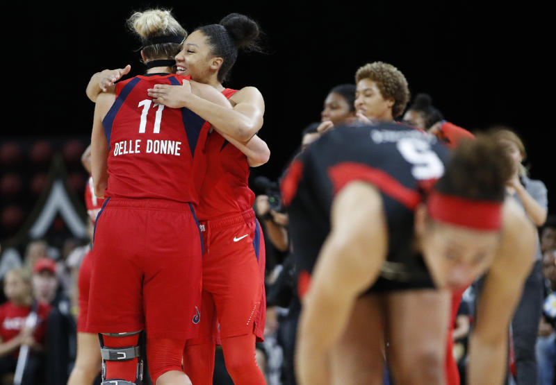 Washington Mystics' Elena Delle Donne, left, and Aerial Powers celebrate after defeating the Las Vegas Aces in Game 4 of a WNBA playoff basketball series Tuesday, Sept. 24, 2019, in Las Vegas. (AP Photo/John Locher)