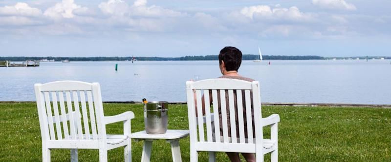 Senior lady in patio chairs drinking champagne by Chesapeake bay