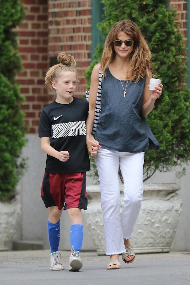 <p>Rusell wore white flared jeans with a gray tank while out with her son, River, in New York. (Photo: AKM-GSI) </p>