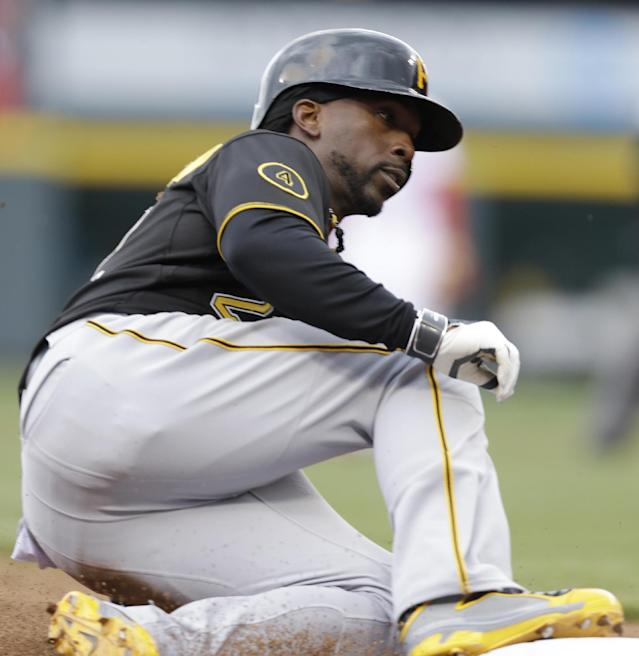 Pittsburgh Pirates' Andrew McCutchen advances to third on a wild pitch by Cincinnati Reds relief pitcher Sam LeCure on Tuesday, April 15, 2014, in the seventh inning of a baseball game that was suspended after six innings Monday evening by rain in Cincinnati. McCutchen scored later in the inning in the game. Pittsburgh won 8-7. (AP Photo/Al Behrman)