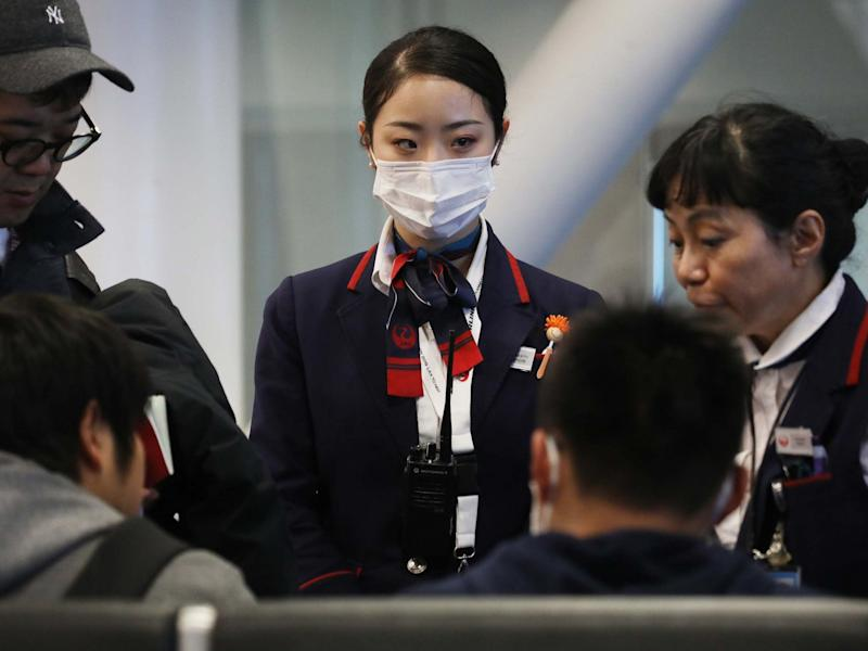 A Japan Airlines worker wears a face mask wile working inside a terminal at Los Angeles International Airport on Thursday: Getty Images