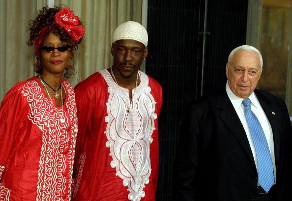 Israeli Prime Minister Ariel Sharon (R) welcomes singer Whitney Houston (L) and her husband/singer, Bobby Brown (C), at the prime minister's residence May 27, 2003 in Jerusalem, Israel. Houston is on a private tour of Israel. (Photo by Quique Kierszenbaum/Getty Images)