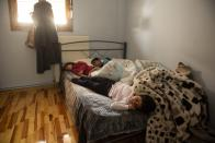 Layan, front, Bayan, back left and Hamsa sleep inside their apartment in the northern city of Thessaloniki, Greece, Saturday, May 1, 2021. Sundered in the deadly chaos of an air raid, a Syrian family of seven has been reunited, against the odds, three years later at a refugee shelter in Greece's second city of Thessaloniki. (AP Photo/Giannis Papanikos)
