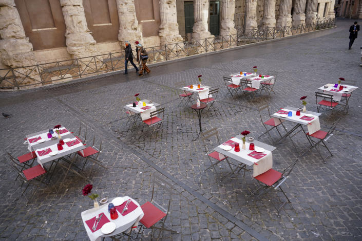 People walk past the empty tables of a caffe', in Rome's central Piazza di Pietra, Wednesday, Nov. 25, 2020. (AP Photo/Andrew Medichini)