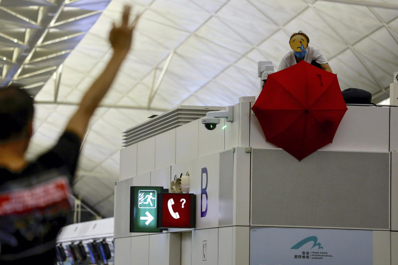A protester uses an umbrella to block a surveillance camera during a demonstration at the Airport in Hong Kong, Tuesday, Aug. 13, 2019. Riot police clashed with pro-democracy protesters at Hong Kong's airport late Tuesday night, a chaotic end to a second day of demonstrations that caused mass flight cancellations at the Chinese city's busy transport hub. (AP Photo/Vincent Yu)