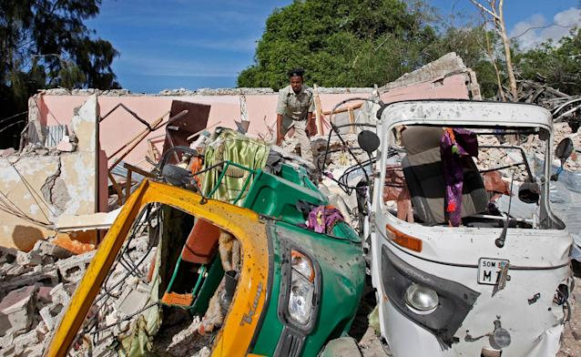 <p>A member of Somalia's security forces walks past destroyed vehicles at the scene of a car bomb blast and gun battle targeting a restaurant in Mogadishu, Somalia Thursday, June 15, 2017. (Photo: Farah Abdi Warsameh/AP) </p>