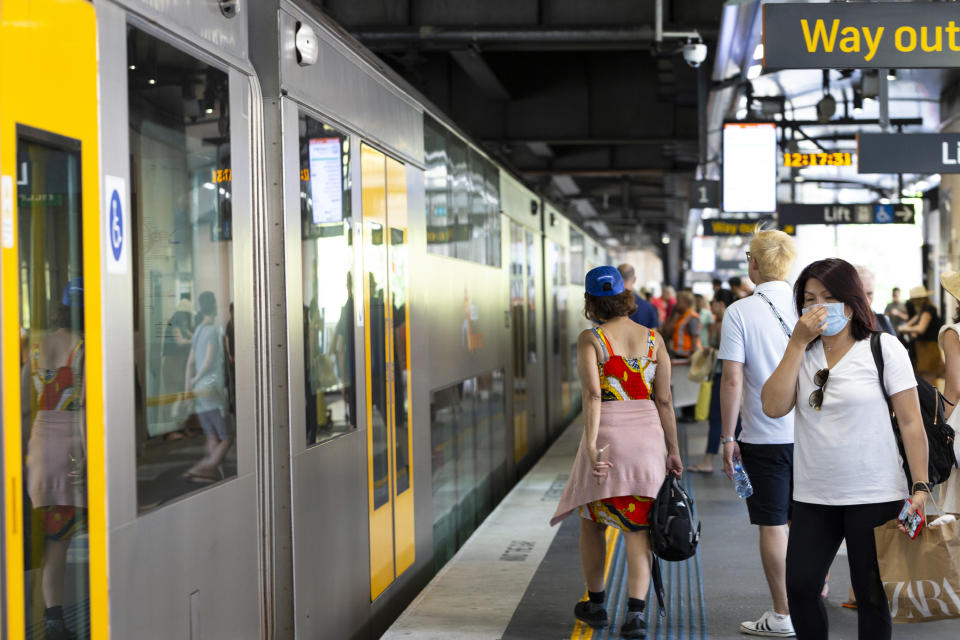Sydney, Australia - March 01, 2020: Circular Quay, young asian woman wearing face mask and other people waiting to board train at Circular Quay train station