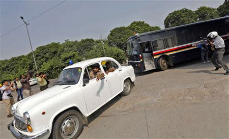 A police bus carrying four men who were found guilty of fatal gang-rape arrives at a court in New Delhi