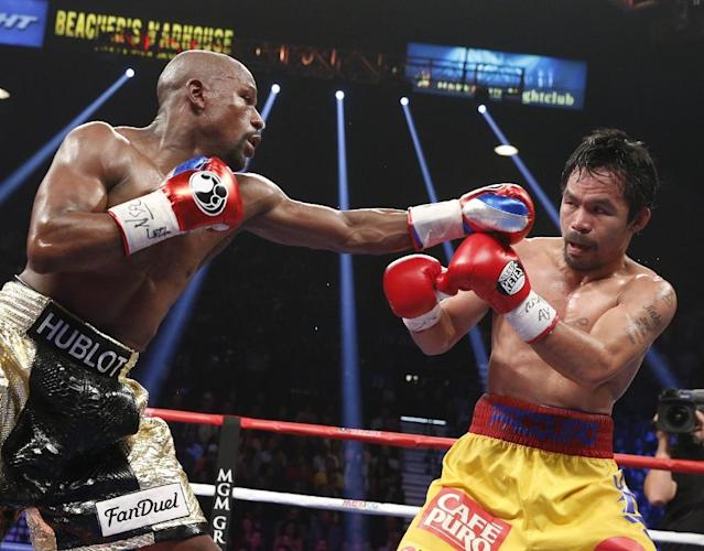 Floyd Mayweather Jr. exchange punches with Manny Pacquiao during their welterweight unification championship bout, May 2, 2015 at MGM Grand Garden Arena in Las Vegas, Nevada. Mayweather defeated Pacquiao by unanimous decision (AFP Photo/John Gurzinski)