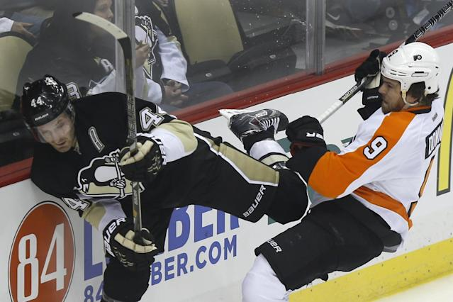 Pittsburgh Penguins' Brooks Orpik (44) and Philadelphia Flyers' Steve Downie (9) collide along the boards during the first period of an NHL hockey game on Sunday, March 16, 2014, in Pittsburgh. (AP Photo/Keith Srakocic)