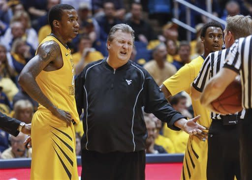 West Virginia coach Bob Huggins, center, speaks to an official in the second half of an NCAA college basketball game against Iowa State at WVU Coliseum in Morgantown, W.Va., on Saturday, March 9, 2013. Iowa State won 83-74. (AP Photo/David Smith)
