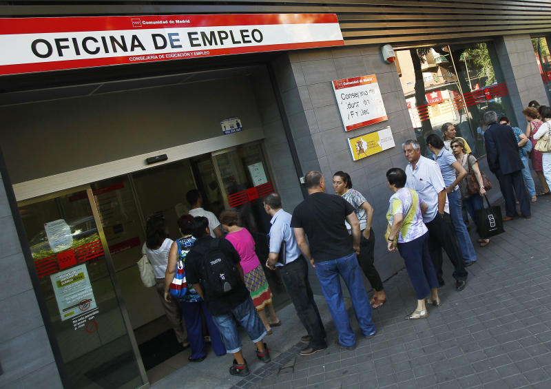 People queue outside an unemployment office in Madrid, Spain, Tuesday, July 3, 2012. The number of people claiming unemployment benefits in Spain went down sharply in June as employers embarked on a hiring spree to prepare for the country's busy summer tourism season. Spain's jobless rate is 52 percent for those under age 25. (AP Photo/Andres Kudacki)