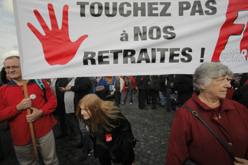 "Protestors hold a banner reading: "" Do not touch our retirements"" during a demonstration in Paris, Tuesday, Oct. 15, 2013. President Francois Hollande has managed to do what was once thought impossible: make changes to France's cherished and generous retirement system with little resistance from unions. His secret? The changes are so small and put off so far into the future that economists say they aren't worthy of the name ""reform."" (AP Photo/Christophe Ena)"
