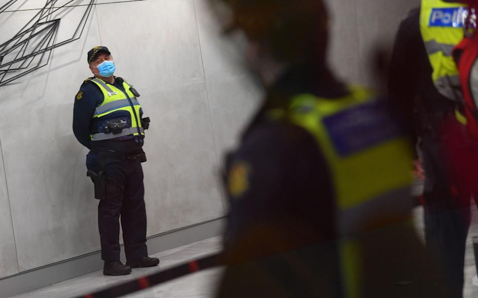 Police and Protective Services officers stand in the foyer of a quarantine hotel - Shutterstock