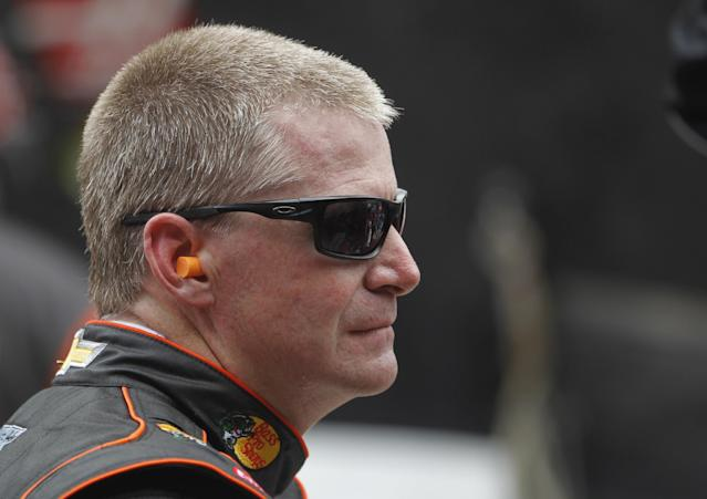 Driver Jeff Burton watches from the wall as his crew works on his car during practice for the Irwin Tools Night Race NASCAR Sprint Cup Series auto race at Bristol Motor Speedway on Friday, Aug. 22, 2014, in Bristol, Tenn. (AP Photo/Wade Payne)