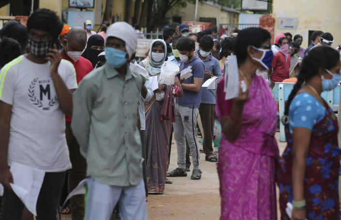 People wait in a queue to give their nasal swab samples to test for the coronavirus at Government Fever Hospital in Hyderabad, India, Wednesday, July 15, 2020. As India's coronavirus caseload approaches 1 million, lockdowns are being reimposed in parts of the country as governments try to shield the health system from being overwhelmed. (AP Photo/Mahesh Kumar A.)