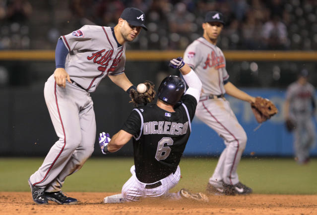 Atlanta Braves second baseman Tommy La Stella (7) drops the ball as Colorado Rockies' Corey Dickerson (6) steals second base in the eighth inning of a baseball game in Denver on Tuesday, June 10, 2014. (AP Photo/Joe Mahoney)