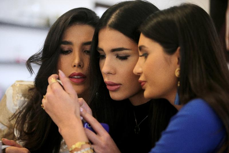"""(L-R) Nadine, Farah and Alice, stars of Lebanese reality TV show """"The Sisters"""", check their Instagram page at their villa in the upscale area of Beit-Misk, northeast of Beirut (AFP Photo/Joseph Eid)"""