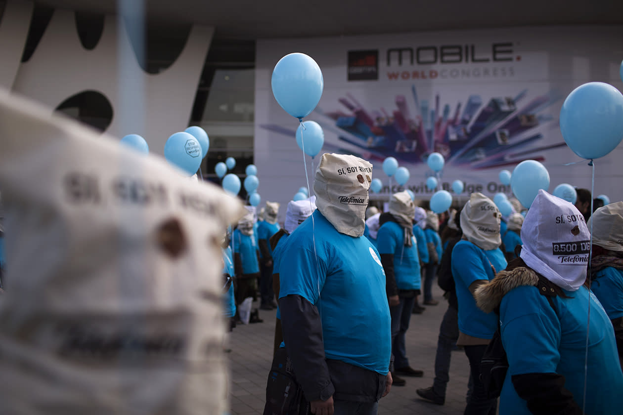 Demonstrators from the Telefonica phone company protest against what they claim are unjustified dismissals from the company, outside the Mobile World Congress, the world's largest mobile phone trade show.