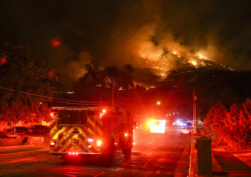 Fire crews head up East Pages Lane as a fire burns on the hill East of Centerville, Utah early Friday, Aug. 30, 2019. Three homes were destroyed and anther eight were impacted with fire damage. An additional 400 homes have been evacuated in the Centerville area. (Colter Peterson/The Deseret News via AP)