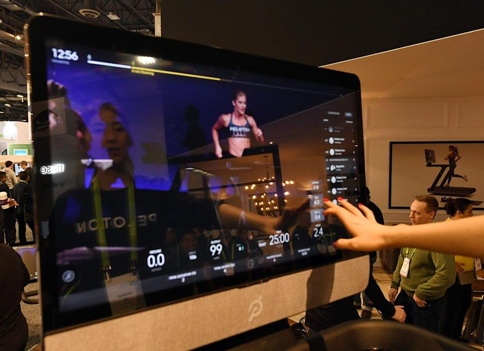 LAS VEGAS, NV - JANUARY 11:  Maggie Lu is reflected in a touch screen as she demonstrates how to select a class on a Peloton Tread treadmill during CES 2018 at the Las Vegas Convention Center on January 11, 2018 in Las Vegas, Nevada. The USD 3,995 workout machine is expected to be available later this year and features a 32-inch touch screen that connects users to instructors giving live or on-demand fitness classes. CES, the world's largest annual consumer technology trade show, runs through January 12 and features about 3,900 exhibitors showing off their latest products and services to more than 170,000 attendees.  (Photo by Ethan Miller/Getty Images)