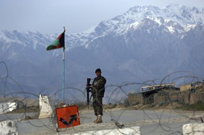 Afghan soldier in fatigues guards a checkpoint, with snow-capped mountains and an Afghan flag in the background