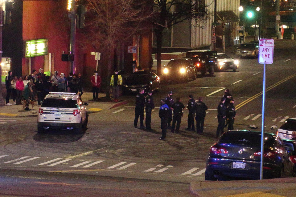 Tacoma Police and other law enforcement stand in a intersection near the site of a car crash Saturday, Jan. 23, 2021, in downtown Tacoma, Wash. At least one person was injured when a police car plowed through a crowd of people Saturday night who were watching a downtown street race, the Tacoma News-Tribune reported. (AP Photo/Ted S. Warren)