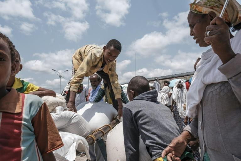 A young person arranges a sack of wheat on a cart during food distribution organized by the Amhara government near the village of Baker in Ethiopia's Tigray region -- US and UN officials are heading there to press for more aid