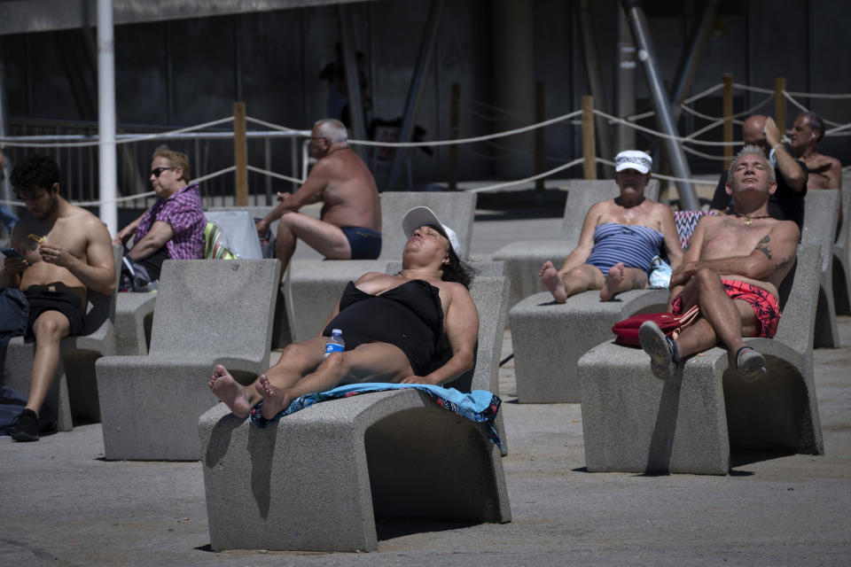 FILE - In this Tuesday, June 8, 2021 file photo, people sunbathe near the beach in Barcelona, Spain. For Europe's battered tourism industry, chaos and confusion over travel rules and measures to contain fresh virus outbreaks are contributing to another cruel summer. Popular destination countries are grappling with surging COVID-19 variants but the patchwork and last-minute nature of the efforts as peak season gets underway threatens to derail another summer. (AP Photo/Emilio Morenatti, File)