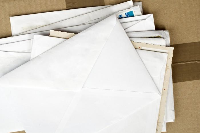 Various envelopes stacked on top of a cardboard shipping box.