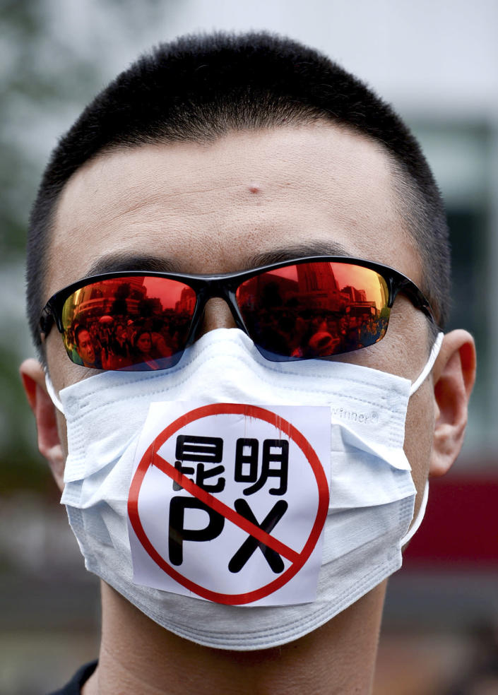 "A Chinese man wears a face mask with the word ""No to Kunming PX,"" paraxylene, written on, takes part in a protest against a planned refinery project in downtown Kunming in southwest China's Yunnan province Saturday, May 4, 2013. After word spread about an environmental protest that was planned for Saturday in the central Chinese city of Chengdu, drugstores and printing shops were ordered to report anyone making certain purchases. Microbloggers say government fliers urged people not to demonstrate, and schools were told to stay open to keep students on campus. Meanwhile, hundreds of people - many wearing mouth masks - gathered in Kunming to protest a planned refinery project in the area. The demonstrators demanded information transparency and that public health be safeguarded. (AP Photo) CHINA OUT"