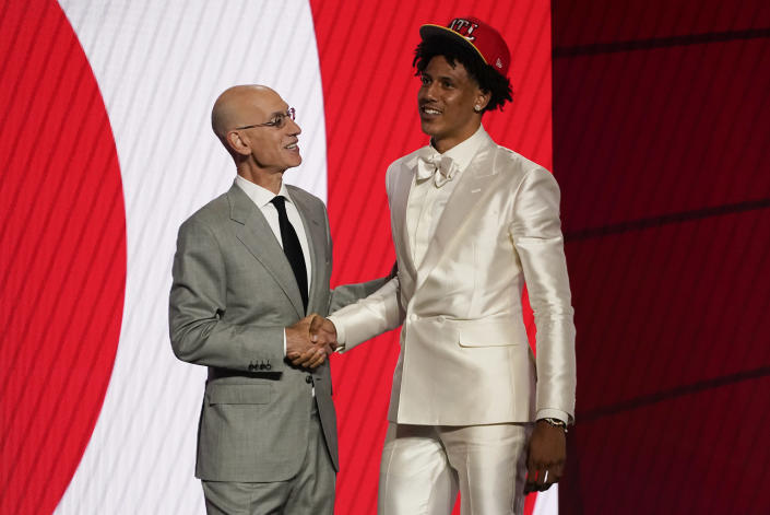 Jalen Johnson, right, greets NBA Commissioner Adam Silver after being selected 20th overall by the Atlanta Hawks during the NBA basketball draft, Thursday, July 29, 2021, in New York. (AP Photo/Corey Sipkin)