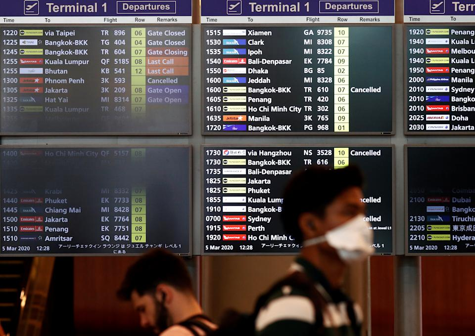 A man wearing a mask passes a flight information board at Changi Airport, following the coronavirus outbreak in Singapore March 5, 2020. REUTERS/Edgar Su