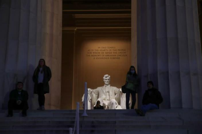 A few people take to the steps at the Lincoln Memorial during the coronavirus disease (COVID-19) outbreak, where normally thousands of Christians would gather for worship at Easter sunrise, in Washington