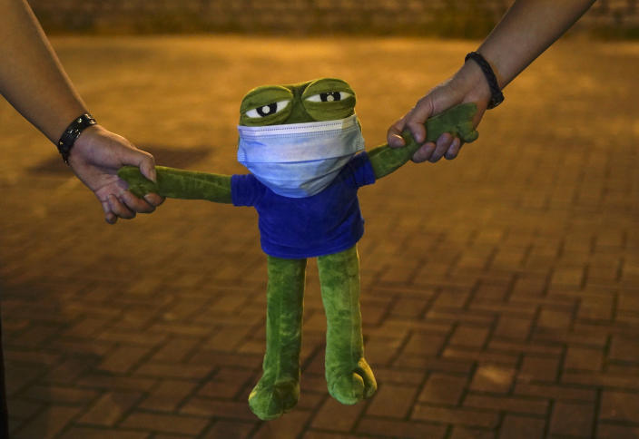 Protesters hold Pepe the frog plush toy, in Hong Kong, Friday, Oct. 18, 2019. Hong Kong pro-democracy protesters are donning cartoon/superheroes masks as they formed a human chain across the semiautonomous Chinese city, in defiance of a government ban on face coverings. (AP Photo/Vincent Yu)
