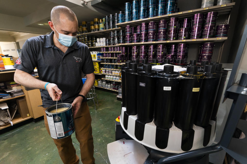 Billy Wommack, purchasing director at the W.S. Jenks & Sons hardware, carries a gallon of paint to a colorant dispenser at the mixing station of the hardware store's paint department, Friday, Sept. 24, 2021, in northeast Washington. (AP Photo/Manuel Balce Ceneta)